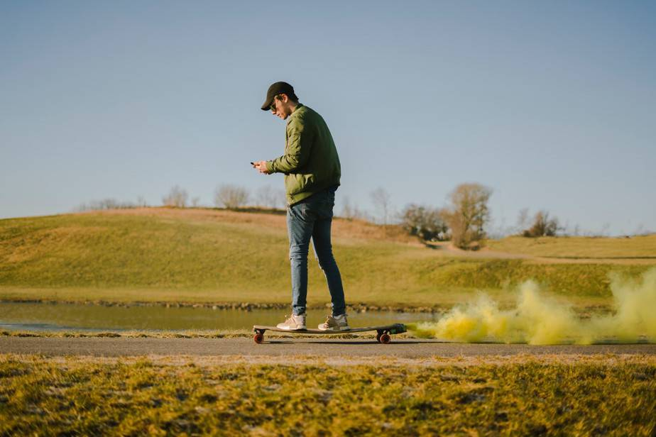 man in green jacket and blue jeans on skateboard